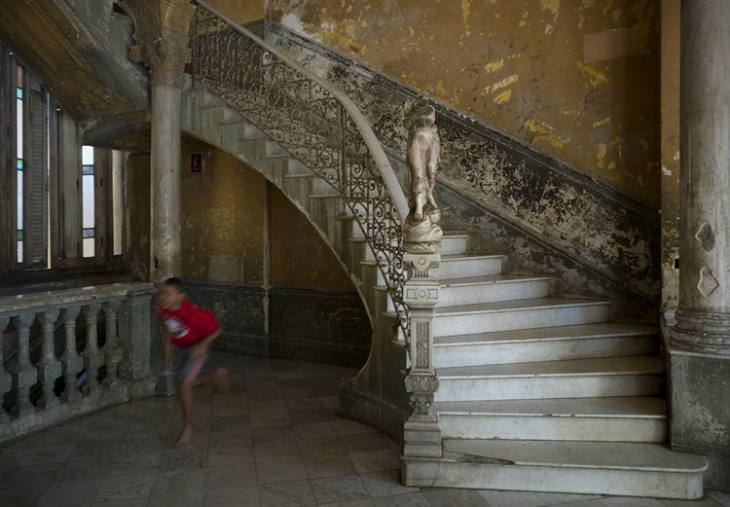 Boy running past a marble staircase, Calle Concordia, Centro, Havana.