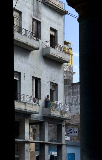 Woman on a balcony above Ave. Simon Bolivar, Havana.